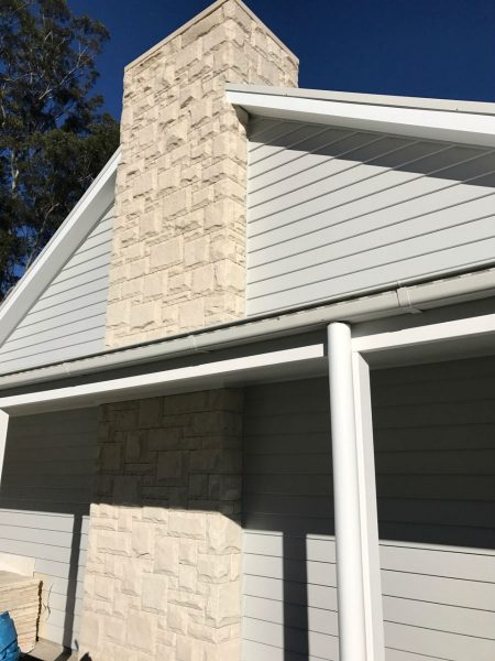 Sandstone chimney as feature of exterior house design.