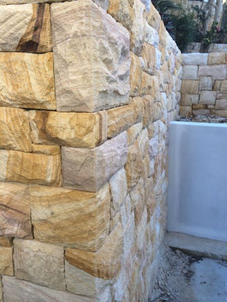 Natural stonework wall utilising sandstone by landscape solutions experts, Central Coast.