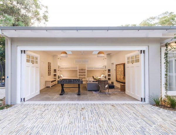 This modern and eye-catching stone flooring driveway by Central Coast landscapers draws a person into the garage-turned studio and indoor entertainment area.