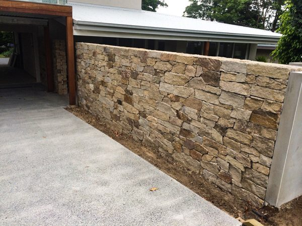 Landscape design and construction on the Central Coast like this stone cladding feature wall for privacy.