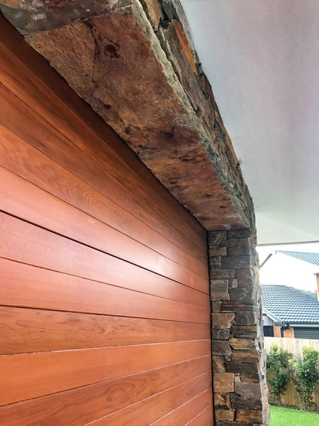 Beautiful stone wall cladding around a garage door, another example of our Central Coast landscape design and construction work