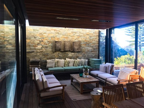 Landscaping solutions can also creep indoors like with this example of a feature stone wall in an indoor-outdoor sitting room by Central Coast landscape designers.