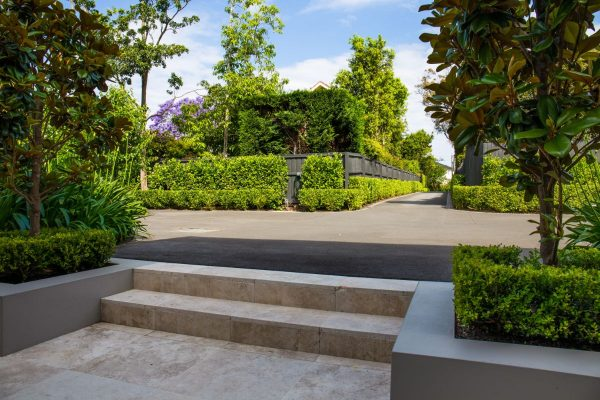 Step down into the the stone entrance of the house; looking back down driveway at beautiful landscaping true in style and grandeur to the Killara surroundings.